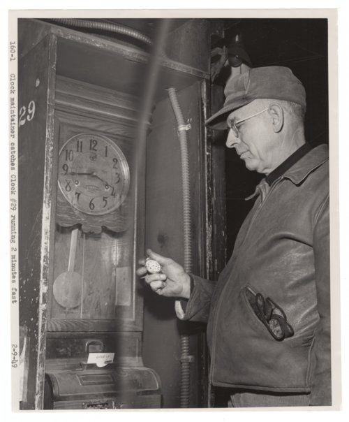 Atchison, Topeka & Santa Fe Railway's clock maintainer checking a clock - Page