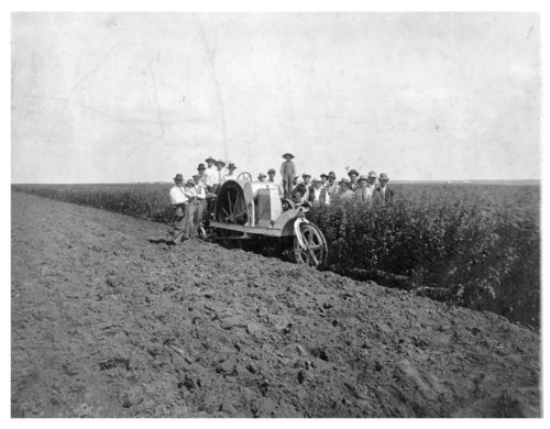 A group of men pose with a tractor in a field in Thomas County, Kansas - Page