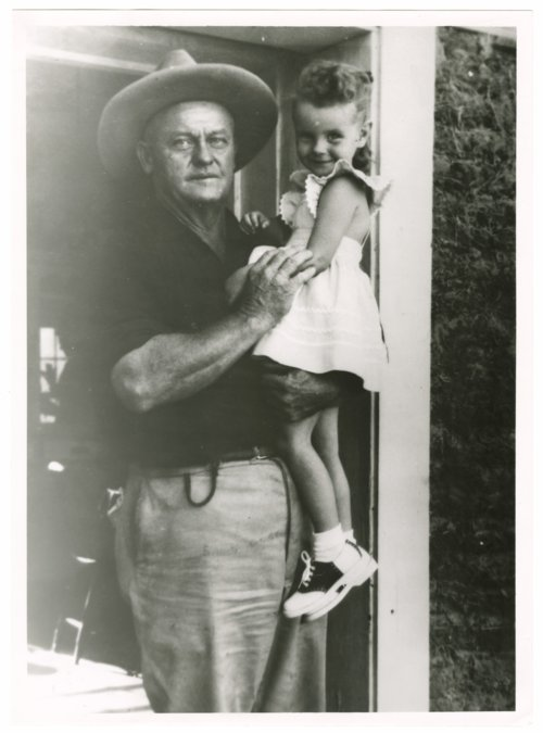 V.A. (Verney A.) Kear, Sod House Museum, poses with a little girl by the door of one of the museum's sod houses, Colby, Thomas County, Kansas - Page