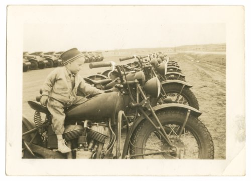 Young boy seated on a motorcycle photograph - Page