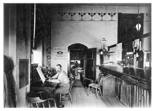 J.S. Huddleston at his desk in the treasurer's office, Logan County, Kansas - Page