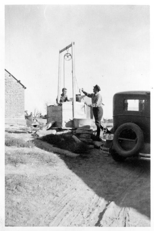 Two men pulling water from a well, Logan County, Kansas - Page