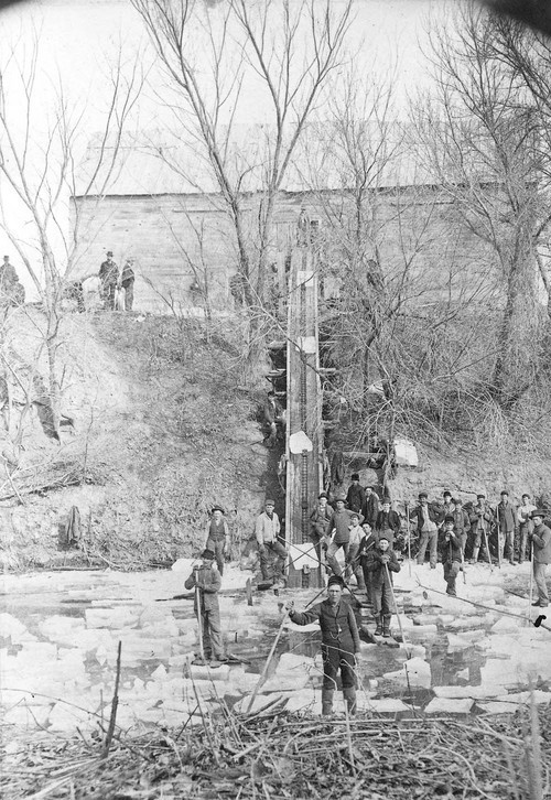 Photograph of men cutting and hauling ice for storage, Pipe Creek, Ottawa County, Kansas.