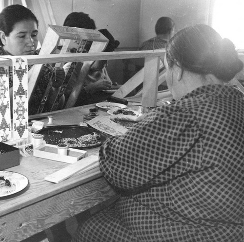 Photograph showing Native American women working with beads in Mayetta, Kansas, part of the Works Progress Administration's crafts program.