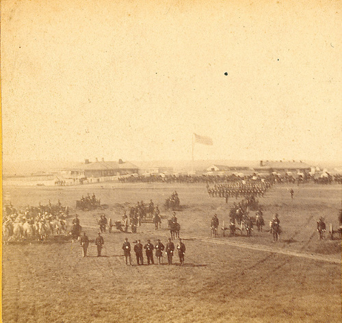 One side of a stereograph showing U.S. Army troops on the  grounds of Fort Harker, 1867