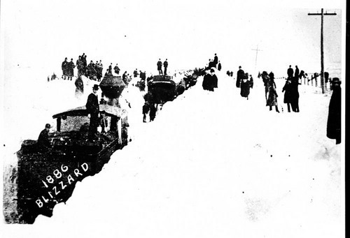 View of steam locomotives trying to cut through large drifts of snow, 1886