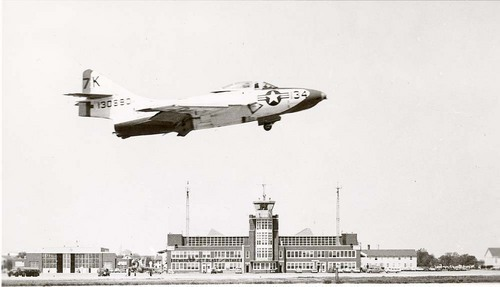View of the main hanger, operations tower, and other facilities at the Naval Air Station in Olathe, 1950s.  A Navy airplane is shown in flight.