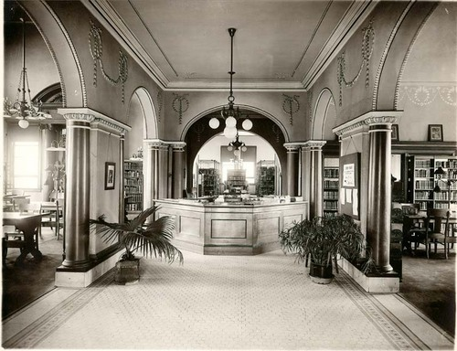 View of the central reference desk and reading room bookshelves in the Leavenworth Public Library, 1911.