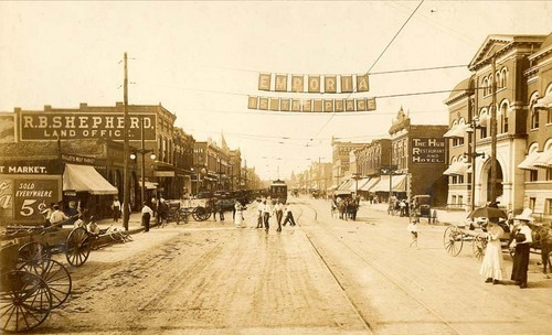 "View of Commercial Street with a banner ""Emporia Is The Place"" hanging between two poles, 1910"