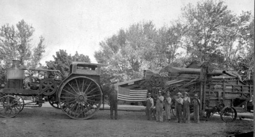 Photograph of of a group of German American farmers standing before a very large steam tractor and threshing machine in Marion County, 1918. An American flag is displayed, suspended between the two machines.