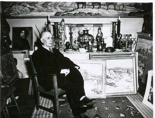 Informal portrait of Birger Sandzen shown seated in his study with samples of his artwork and art collection