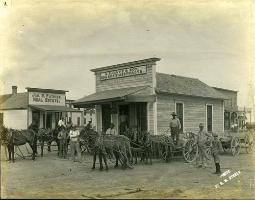 View of workers using wagons and mules to move S. E. Cave's office building from Santa Fe to the new county seat in Sublette, Kansas